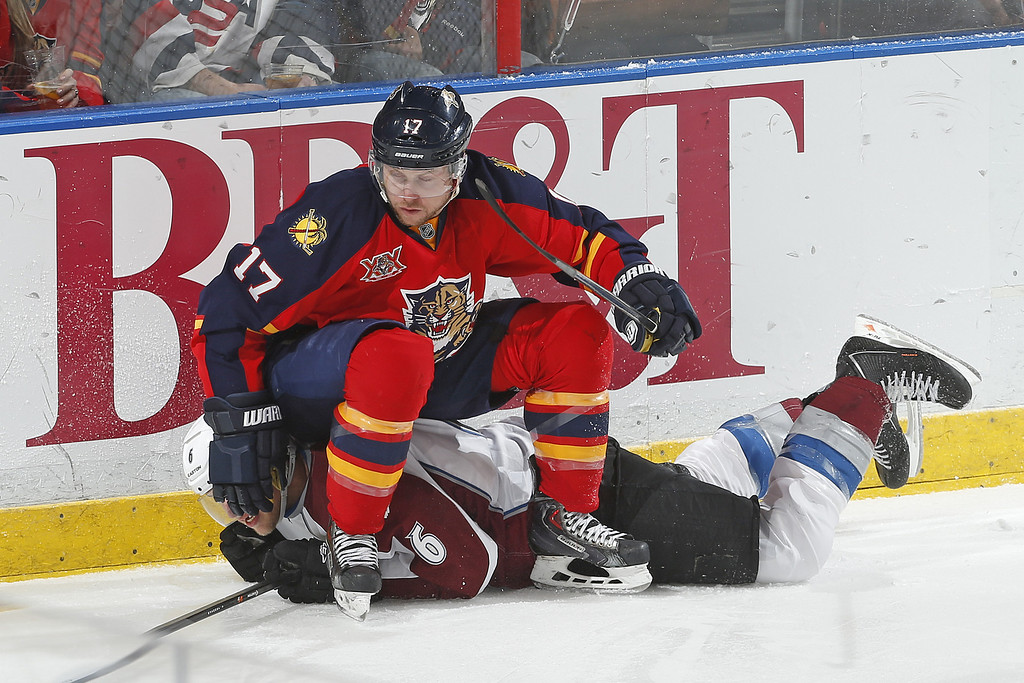 . SUNRISE, FL - JANUARY 24: Jesse Winchester #17 of the Florida Panthers sits on top of Erik Johnson #6 of the Colorado Avalanche after checking him along the boards at the BB&T Center on January 24, 2014 in Sunrise, Florida. The Avalanche defeated the Panthers 3-2. (Photo by Joel Auerbach/Getty Images)
