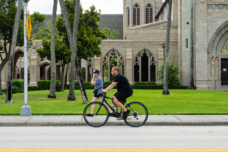 A woman walks in front of the Church of Bethesda-by-the-Sea as man passes her on his bike on S. County Road, Friday, April 24, 2020. Bethesda-by-the-Sea has been closed due to the coronavirus pandemic. [JOSEPH FORZANO/palmbeachdailynews.com]