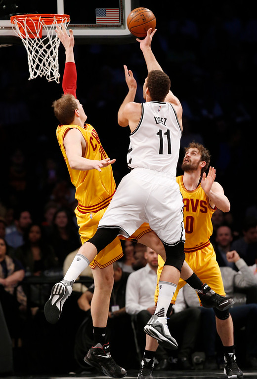 . Brooklyn Nets center Brook Lopez (11) shoots over Cleveland Cavaliers center Timofey Mozgov (20) as Cleveland Cavaliers forward Kevin Love (0) watches from the floor in the first half of an NBA basketball game, Thursday, March 24, 2016, in New York. (AP Photo/Kathy Willens)