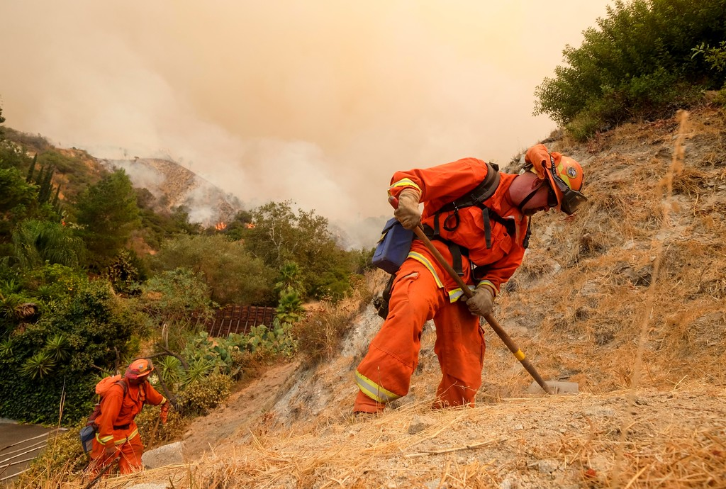 . Member with California Department of Forestry and Fire Protection (Cal Fire) battles a brushfire on the hillside in Burbank, Calif., Saturday, Sept. 2, 2017. Several hundred firefighters worked to contain a blaze that chewed through brush-covered mountains, prompting evacuation orders for homes in Los Angeles, Burbank and Glendale. (AP Photo/Ringo H.W. Chiu).
