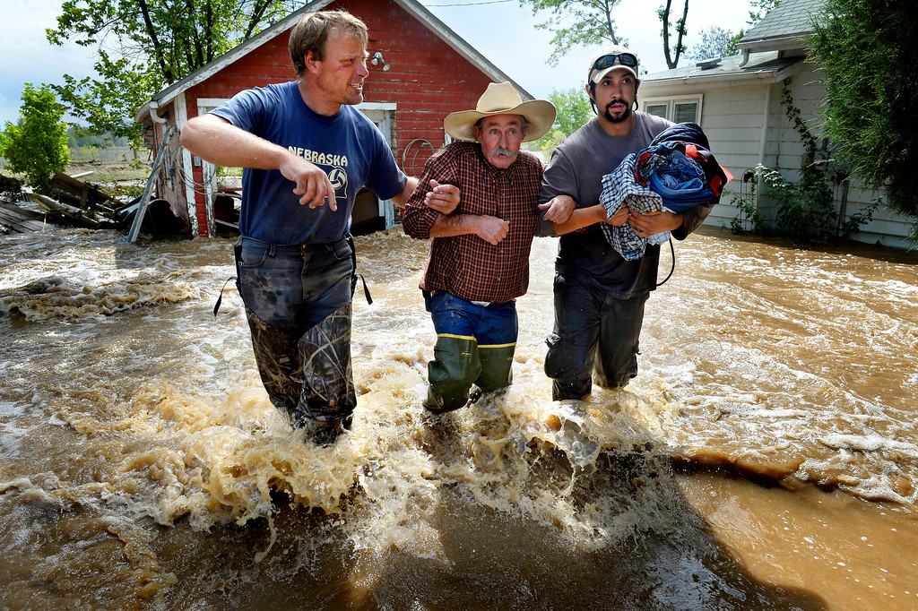 . Dan Hull, center, is assisted by Brian Marquedt, left, and Scott Johnson after rescuing Hull\'s two cats and gathering some items from his flooded home on Hygiene Road in Hygiene,  CO September 14, 2013.  (Photo By Craig F. Walker / The Denver Post)
