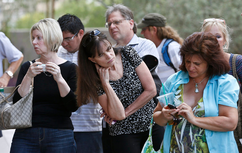 . Curious onlookers check their cellphones and listen in on conversations in front of Maricopa County Superior Court Monday, May 6, 2013, in Phoenix. A Phoenix jury is on its second day of deliberations in the trial of Jodi Arias, who is accused of murdering her one-time boyfriend in Arizona. (AP Photo/Ross D. Franklin)