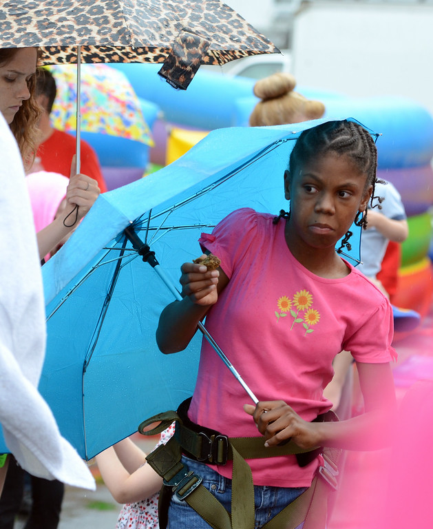 . Sharon Smith ,10, holds an umbrella as rain falls during the Lansdale Founders Day celebration on Saturday August 23,2014. Photo by Mark C Psoras/The Reporter