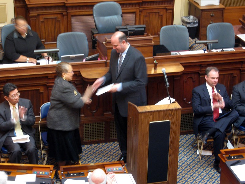 President of the Electoral College Michael Jon Khandelwal hands a sealed certificate of votes to Virginia State Board of Elections Chair Jean Cunningham, for preservation in the Board's archives