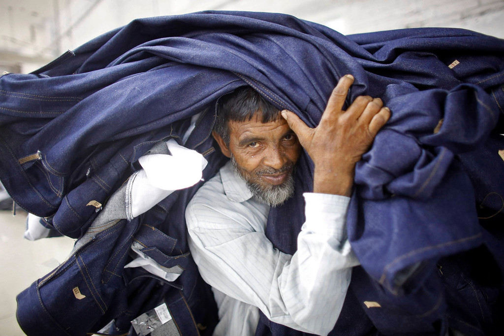 . A worker carries a stack of clothes in a garment factory near the collapsed Rana Plaza building in Savar, Bangladesh June 16, 2013. The April 24 collapse of the Rana Plaza complex, built on swampy ground outside Dhaka with several illegal floors, killed 1,132 workers and focused international attention on sometimes lax safety standards in Bangladesh\'s booming garment industry. At least five different Bangladesh agencies have dispatched teams to start inspecting the country\'s thousands of garment factories, but there has been little coordination between them. More than four million people, mostly women, work in Bangladesh\'s clothing sector, which is the country\'s largest employment generator, with annual exports worth $21 billion.  REUTERS/Andrew Biraj