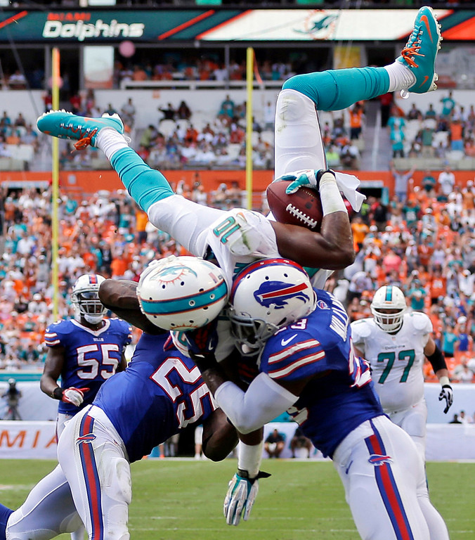 . Miami Dolphins wide receiver Brandon Gibson (10) jumps over Buffalo Bills free safety Aaron Williams (23) and strong safety Da\'Norris Searcy (25) for a touchdown during the first half of an NFL football game, Sunday, Oct. 20, 2013, in Miami Gardens, Fla. (AP Photo/Lynne Sladky)