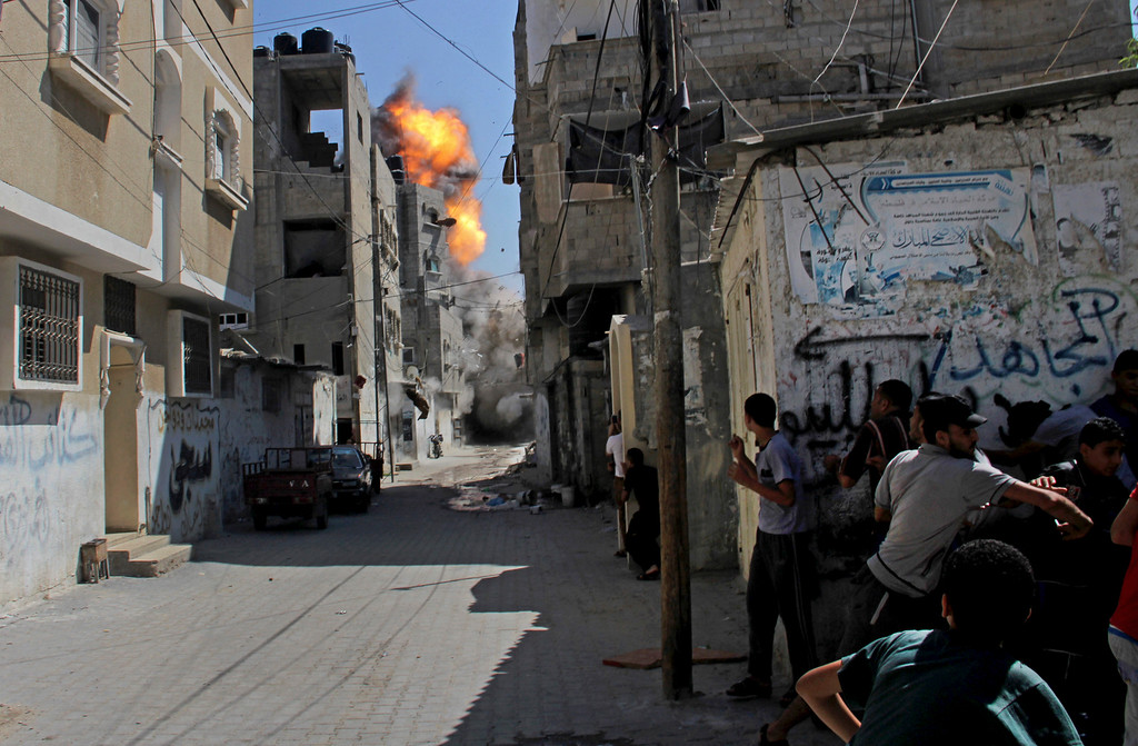 . Palestinians take cover as an Israeli strike on a building causes a ball of fire and smoke to rise in the Rafah refugee camp, southern Gaza Strip, Saturday, Aug. 23, 2014. (AP Photo/Hatem Ali, File)
