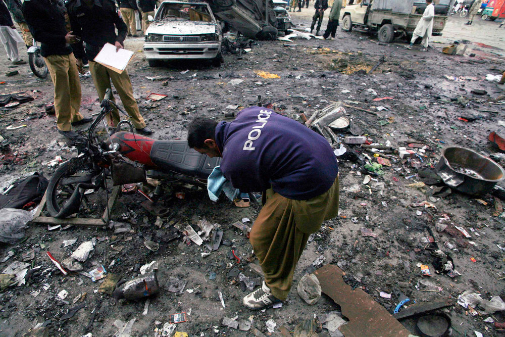 . A bomb disposable squad member checks the site of a blast in Quetta January 10, 2013. A bomb blast in a crowded marketplace killed 11 people and injured more than 40 in Pakistan\'s eastern provincial capital of Quetta on Thursday and a local militant group claimed responsibility, police said. REUTERS/Naseer Ahmed