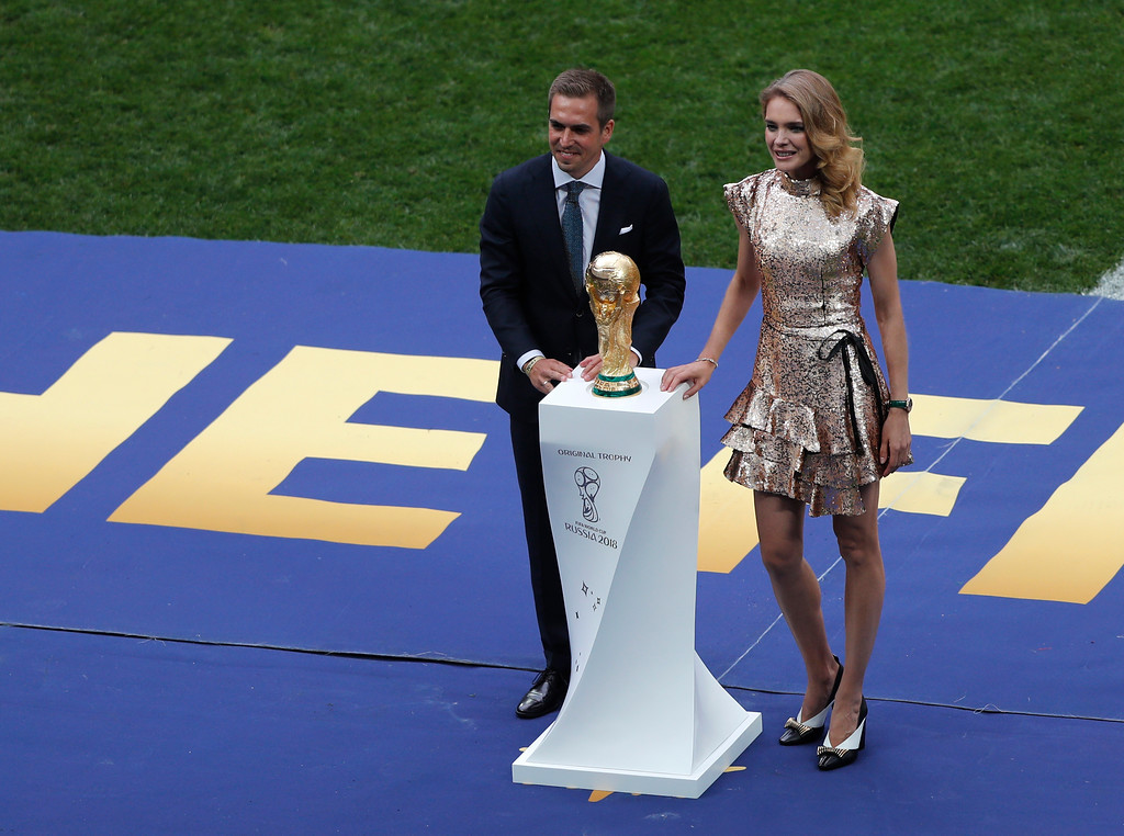 . Former German soccer team captain Philipp Lahm and Russian model Natalia Vodianova display the trophy before the final match between France and Croatia at the 2018 soccer World Cup in the Luzhniki Stadium in Moscow, Russia, Sunday, July 15, 2018. (AP Photo/Frank Augstein)