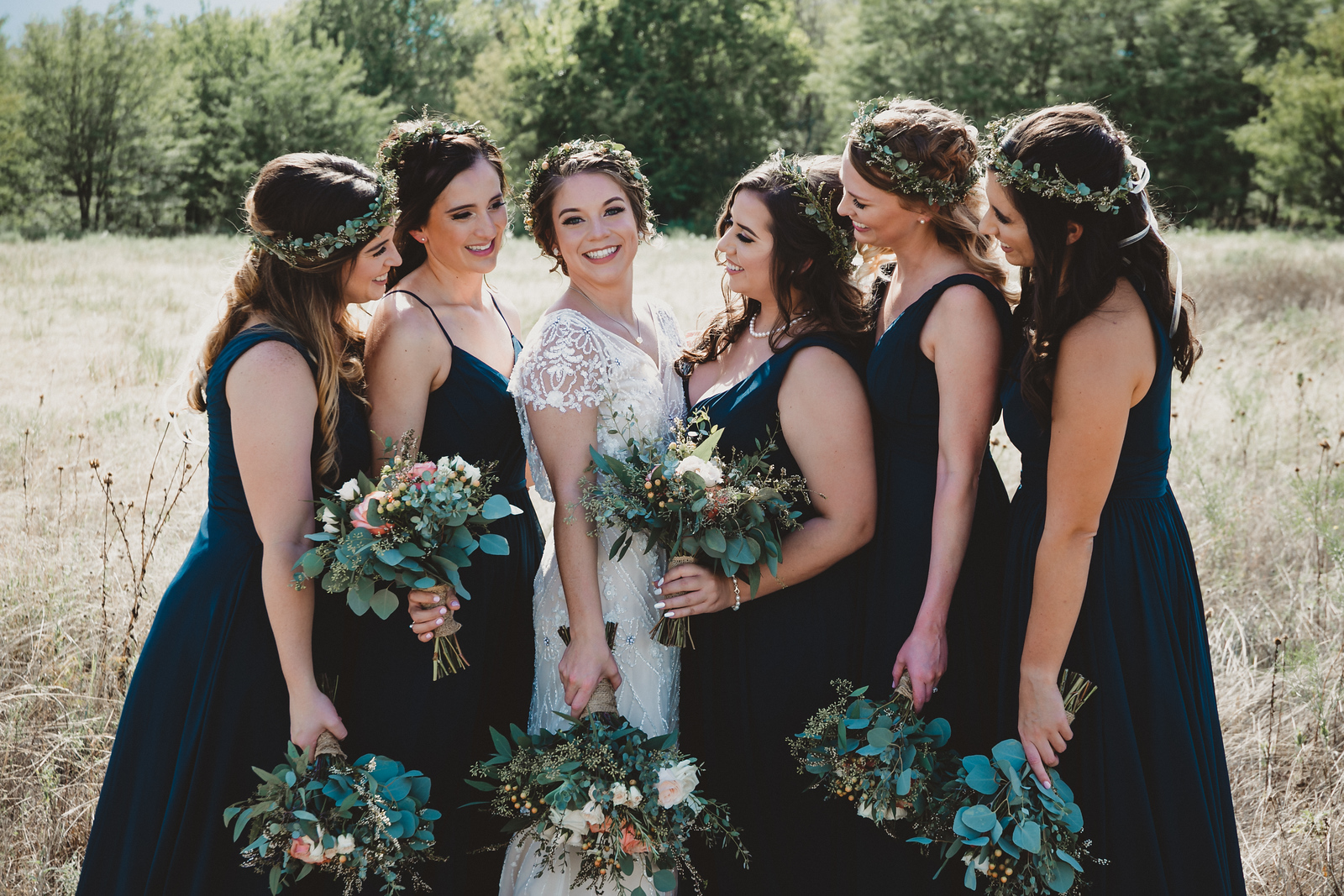 A bride wearing a lace wedding is surrounded by her five bridesmaids wearing green dresses