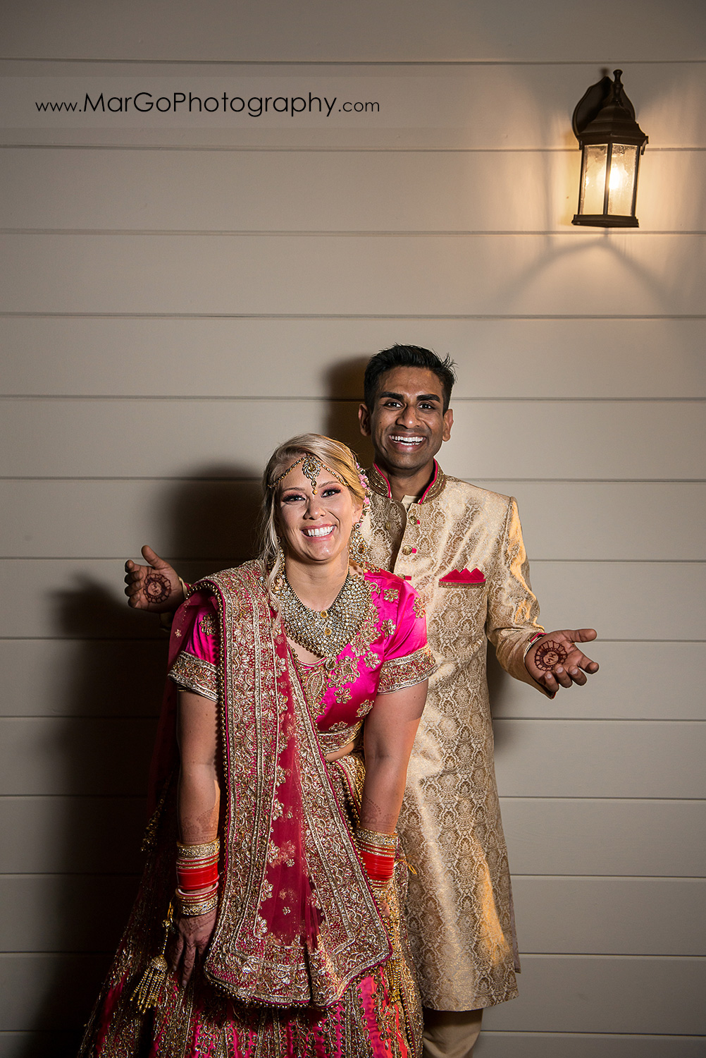 Indian bride and groom in golden and pink outfits on the white wall at Elliston Vineyards in Sunol