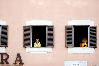 A lady looked out from her window. Street performers performed down in the streets