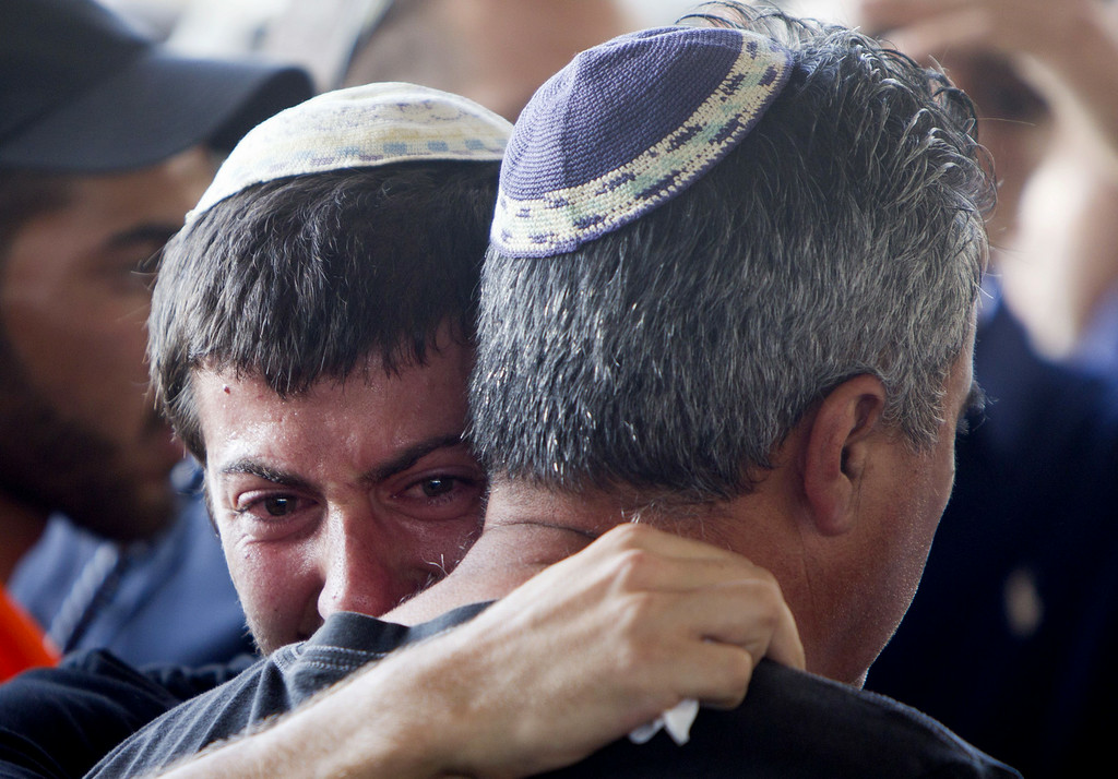 . Relatives of Dror Khenin grieve on July 16, 2014, during his funeral in Yehud, east of Tel Aviv, the day after he was killed when a short-range rocket fired by Palestinian militants landed near the border with the Gaza Strip where he was delivering food to the Israeli soldiers. He is the first Israeli civilian killed during Israel\'s Operation Dove. Israel\'s campaign, now in its ninth day, has killed 214 Palestinians, with a Gaza-based rights group saying over 80 percent of them were civilians. AFP PHOTO/AHMAD  GHARABLI/AFP/Getty Images