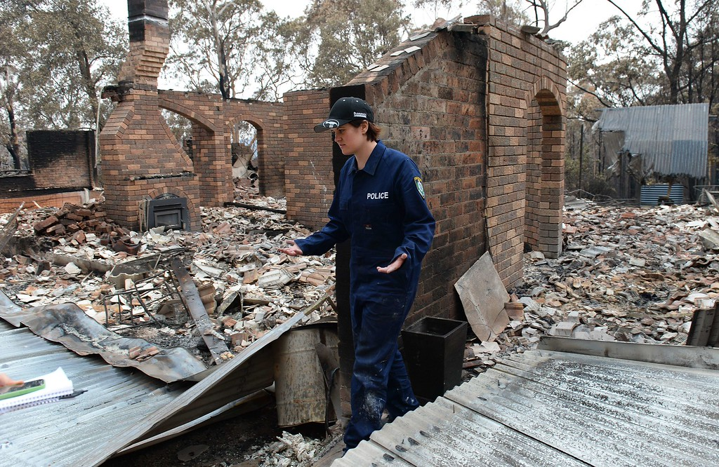 . Policewoman Tegan Mobbs looks at the remains of her home in Yellow Rock in the Blue Mountains on October 22, 2013, after it was destroyed in a firestorm which tore through the area.   The granite slabs that were once a kitchen bench are still warm five days and a chimney stack and fireplace are all that remain upright in the ruins of what was once a five-bedroom home on a picturesque five-acre bush block in Yellow Rock, west of Sydney.  AFP PHOTO/William WEST/AFP/Getty Images