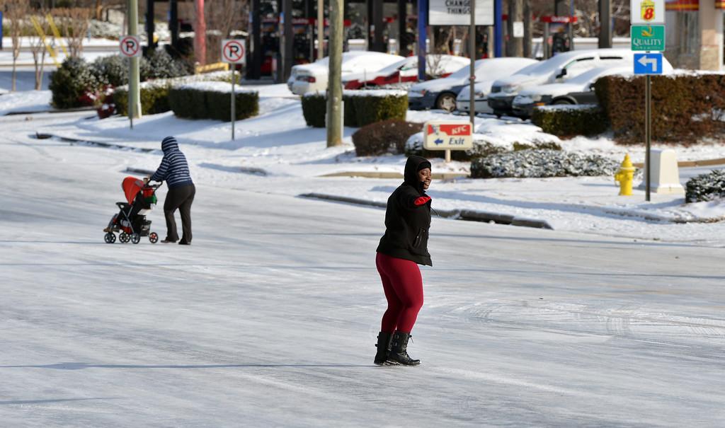 . Pedestrians cross a snow and ice covered roadway in the metro-Atlanta city of Lithonia, Georgia, USA, 29 January 2014.  EPA/KENT D. JOHNSON / ATLANTA JOURNAL CONSTITUTION