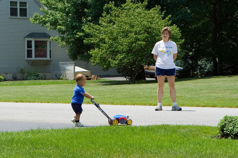 K.C. pushes his bubble mower at the end of the driveway under the watchful eye of his Mom.