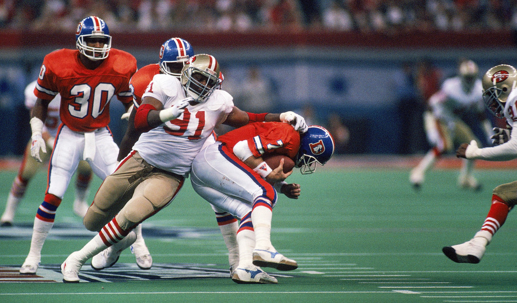 . Defensive end Larry Roberts #91 of the San Francisco 49ers sacks Denver Broncos quarterback John Elway #7 in Super Bowl XXIV at Louisiana Superdome on January 28, 1990 in New Orleans, Louisiana.   (Photo by George Rose/Getty Images)