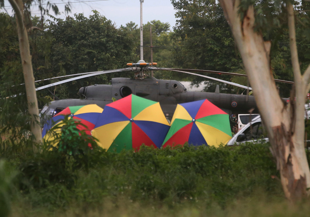 . Local police place umbrellas around an evacuation helicopter as the remaining trapped boys and their coach are extracted from a cave in Mae Sai, Chiang Rai province, northern Thailand on Tuesday, July 10, 2018. (AP Photo/Sakchai Lalit)