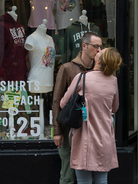 Couples kissing on street in front of the clothing store, Galway City, County Galway, Ireland