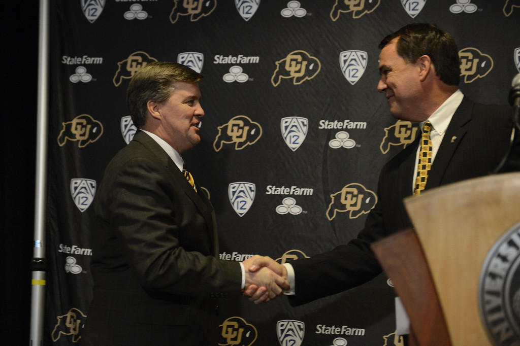 . The University of Colorado at Boulder introduced Mike MacIntyre shakes hands with Athletic Director Mike Bohn at a press conference Monday, December 10, 2012  at the Byron White Club Room at Folsom Field. MacIntyre will be the 25th full-time head football coach in the CU history as he comes from San Jose State. John Leyba, The Denver Post