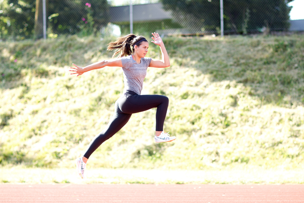 fitness model jumping on track and field