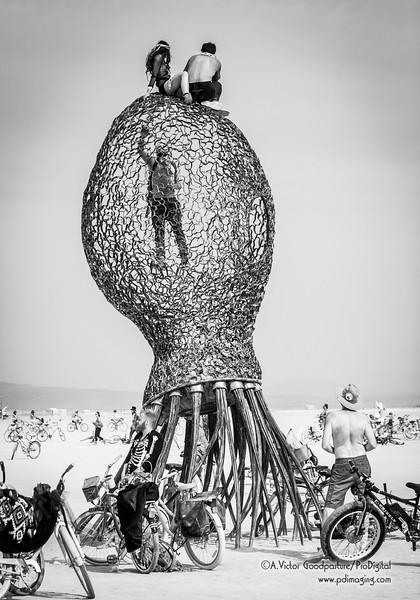 Burners climb atop an art piece.