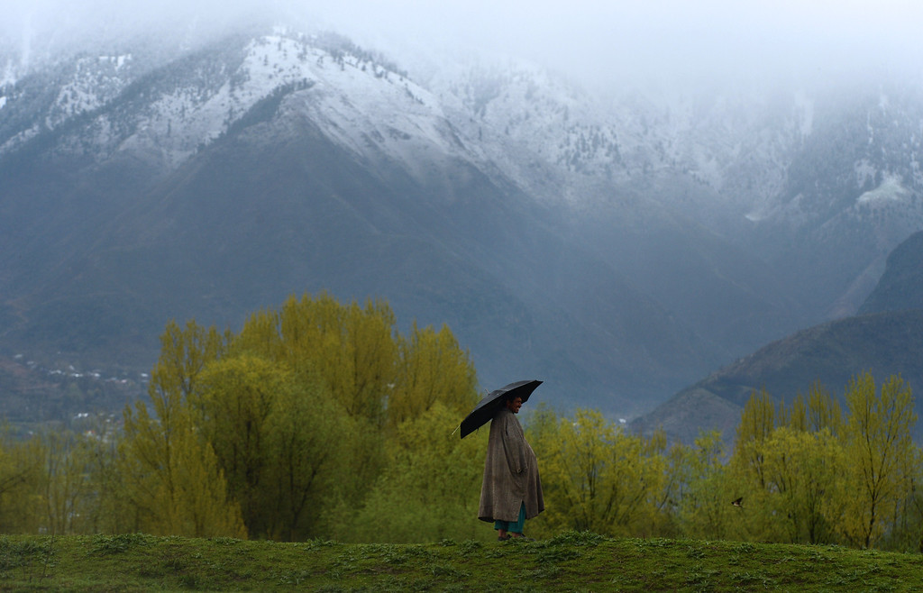 . TOPSHOTS  A Kashmiri shepherd uses an umbrella for shelter as rain falls at the edge of Zabarwan Forest on the outskirts of Srinagar on April 3,2013.    Tourists arrivals are picking up int he Himalayan state after a sharp fall in the wake of protests over the hanging of Kashmiri activist Afzal Guru in February, for an attack on India\'s parliament in 2001.   AFP PHOTO/Tauseef MUSTAFATAUSEEF MUSTAFA/AFP/Getty Images