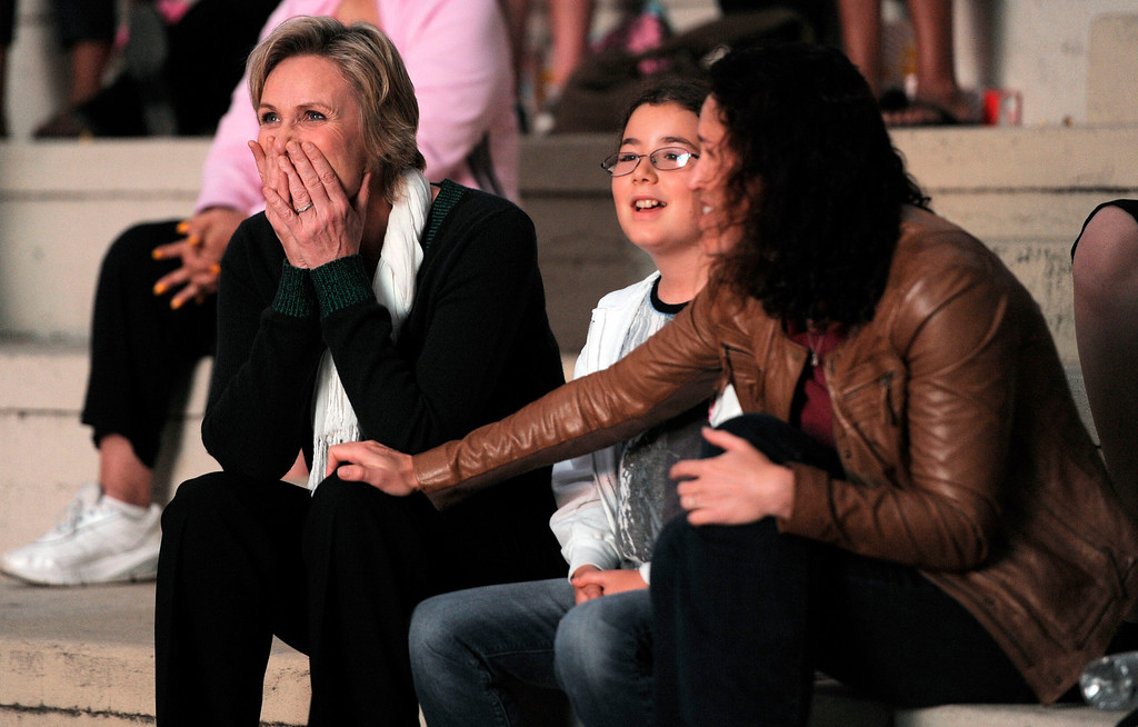 """. Jane Lynch, left, a cast member in the television series \""""Glee,\"""" reacts as she watches herself in a scene from the show during the \""""Glee Sing-A-Long\"""" event at Santa Monica High School in Santa Monica, Calif., Monday, Aug. 15, 2011. Sitting next to Lynch are her wife Dr. Lara Embry and Embry\'s daughter Haden. Musical numbers from the second season of the show were screened for fans and Academy of Television Arts & Sciences members. (AP Photo/Chris Pizzello)"""