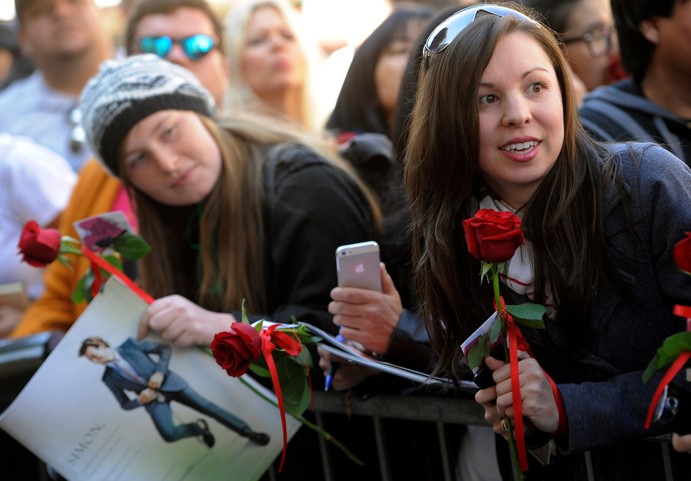 Description of . Diedra Robinson, right, of Birmingham, Alabama, and other fans hold Valentine's Day roses for Australian actor Simon Baker to sign following a ceremony to award him a star on the Hollywood Walk of Fame, on Thursday, Feb. 14, 2013 in Los Angeles. (Photo by Chris Pizzello/Invision/AP)