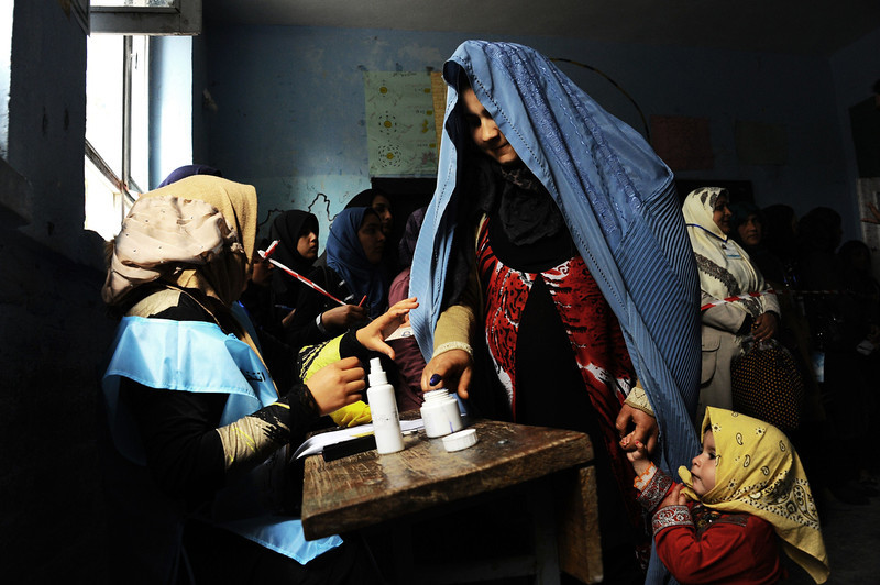 . An Afghan woman (R) is guided by an official as she puts her finger in ink at a polling station in the northwestern city of Herat on April 5, 2014. Afghan voters went to the polls to choose a successor to President Hamid Karzai, braving Taliban threats in a landmark election held as US-led forces wind down their long intervention in the country. (Aref Karimi/AFP/Getty Images)