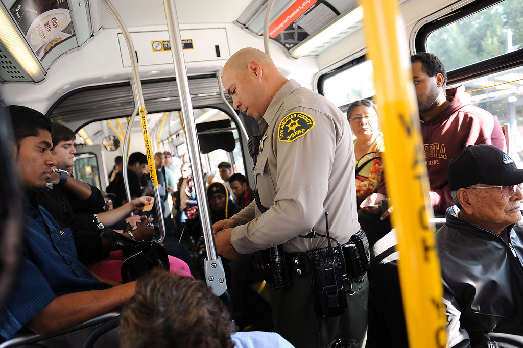 . LA County Sheriff deputy Carlos Valencia boards a bus to check riders TAP cards during an Orange Line fare enforcement operation at the Van Nuys Orange Line Station February 25, 2014.  Officials from Metro and the Los Angeles Sheriff\'s Department Transit Services Bureau announced a new two-pronged effort to cut down on fare-evaders on the Orange Line by improving communications and beefing up enforcement.(Andy Holzman/Los Angeles Daily News)