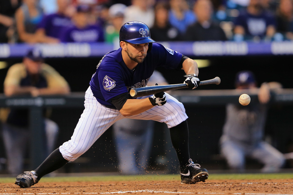. DENVER, CO - JULY 26:  Tyler Chatwood #32 of the Colorado Rockies makes a sacrifice bunt against the Milwaukee Brewers in the fourth inning at Coors Field on July 26, 2013 in Denver, Colorado.  (Photo by Doug Pensinger/Getty Images)