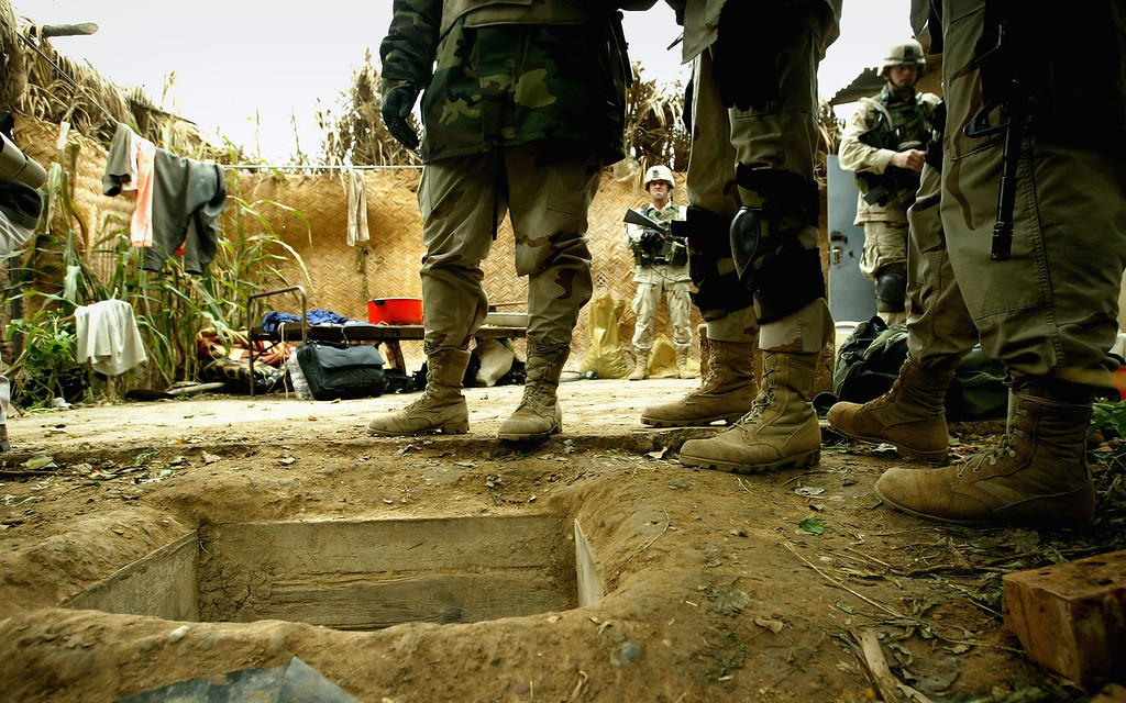 """. American soldiers in the 4th Infantry Division stand over the opening of the \""""spider hole\"""" where Saddam Hussein was captured December 15, 2003 in Ad Dawr, Iraq. Iraq\'s notorious dictator was captured in a raid at the compound on December 13, 2003. (Photo by Chris Hondros/Getty Images)"""
