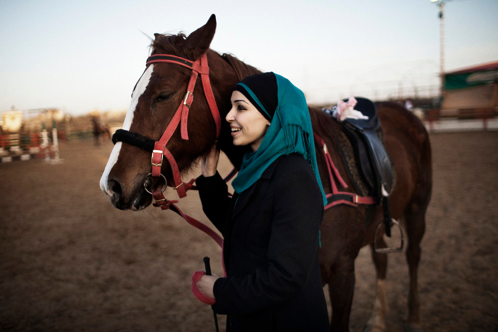 Description of . Hanan Abu Nada, 28, a Palestinian lawyer from Gaza City, stands with her horse at the Al-Furusia riding centre in Gaza City on January 10, 2012. Opened since 2002 but under a new management for the past few months, the centre caters to a small number of women who practice horse riding despite the strict social and cultural norms in the Hamas-run strip. MARCO LONGARI/AFP/Getty Images