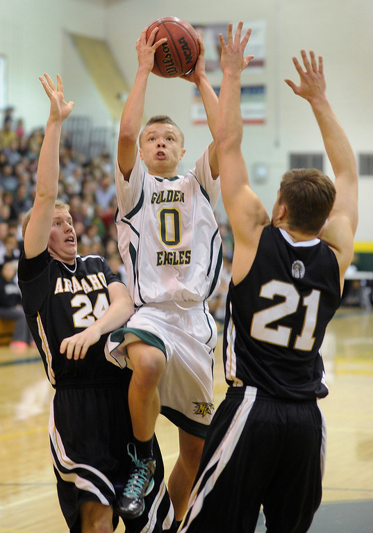 . Golden Eagles senior guard Damani Respass (0) split Arapahoe defenders Brandan Till (24) and Mitch Albyn (21) on the way to the basket in the first half. The Mountain Vista High School boy\'s basketball team hosted Arapahoe Friday night January 4, 2013.  Karl Gehring/The Denver Post