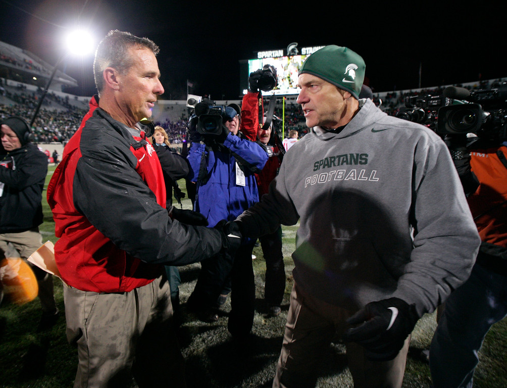 . Ohio State coach Urban Meyer, left, and Michigan State coach Mark Dantonio shake hands following an NCAA college football game, Saturday, Nov. 8, 2014, in East Lansing, Mich. Ohio State won 49-37. (AP Photo/Al Goldis)