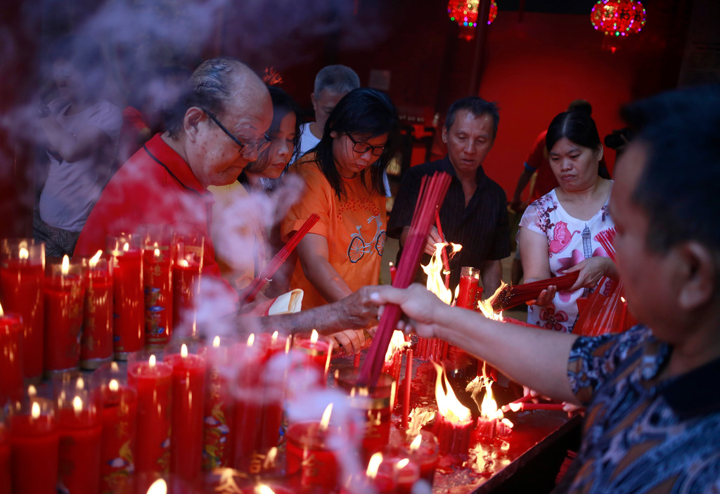 . Indonesian ethnic Chinese light incense sticks during the celebration of Lunar New Year at a temple in the China Town in Jakarta, Indonesia, Friday, Feb. 16, 2018. The celebration marked the beginning of the Year of the Dog in Chinese calendar. (AP Photo/Dita Alangkara)