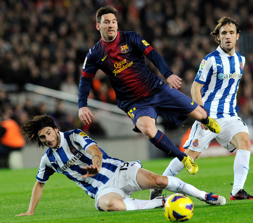 . Barcelona\'s Lionel Messi (C) fights for the ball with Espanyol\'s Diego Colotto (L) during their Spanish First division soccer league match at Camp Nou stadium in Barcelona January 6, 2013. REUTERS/Sergio Carmona