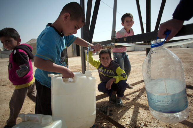 . In this Thursday April 17, 2014 photo, Syrian boys fill containers with drinking water at Zaatari refugee camp, near the Syrian border in Jordan. (AP Photo/Khalil Hamra)