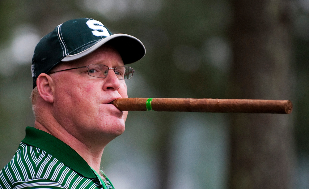 . Brian Sebolt of East Lansing, Michigan holds a big cigar as he watches golfers on the first fairway during a practice round before the 2012 Masters Golf Tournament at Augusta National Golf Club April 3, 2012 in Augusta, Georgia. Play is scheduled to begin April 5, 2012. TOPSHOTS / AFP PHOTO / DON EMMERT