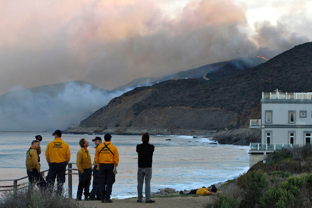 . Firefighters stand on a bluff as the Springs Fire burns in the early morning near Pacific Coast Highway at Point Mugu State Park, May 3, 2013. REUTERS/Jonathan Alcorn