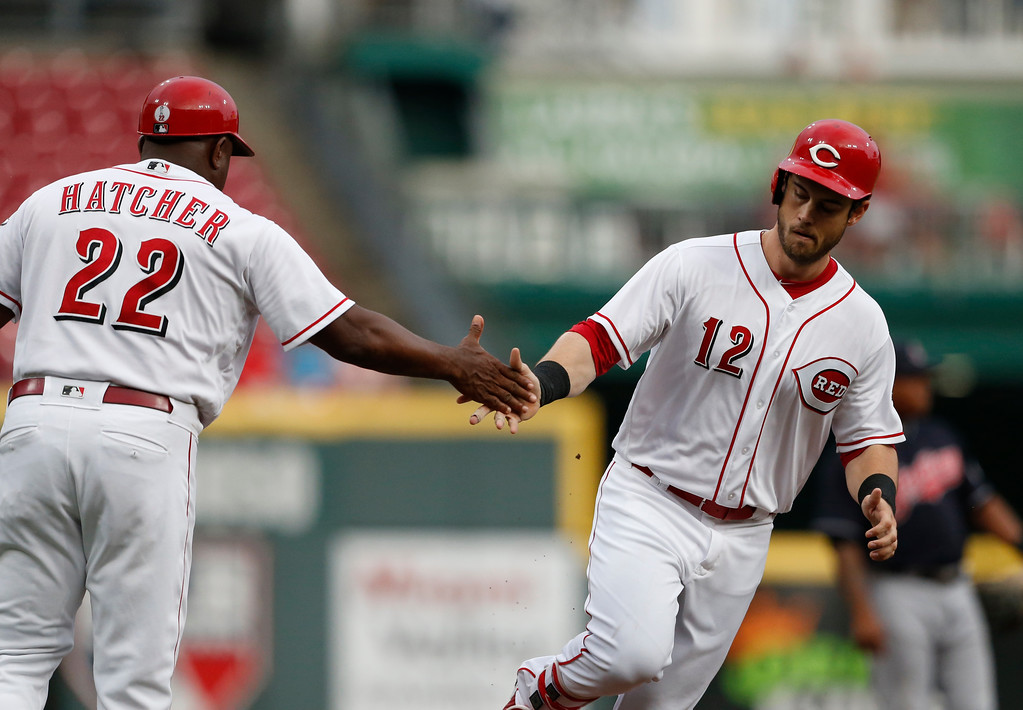. Cincinnati Reds\' Preston Tucker (12) is congratulated on a two-run home run off Cleveland Indians starting pitcher Shane Bieber by third base coach Billy Hatcher (22) during the first inning of a baseball game Wednesday, Aug. 15, 2018, in Cincinnati. (AP Photo/Gary Landers)