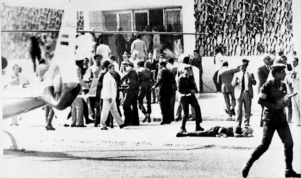 . Egyptian security forces crowd around the doorway of a building in Cairo, Oct. 6, 1981, where Egyptian President Anwar Sadat was taken after he was shot while watching the military parade.  Sadat was taken away from the parade via helicopter, left, while the body of a slain security guard lies on the ground at right.  (AP Photo)