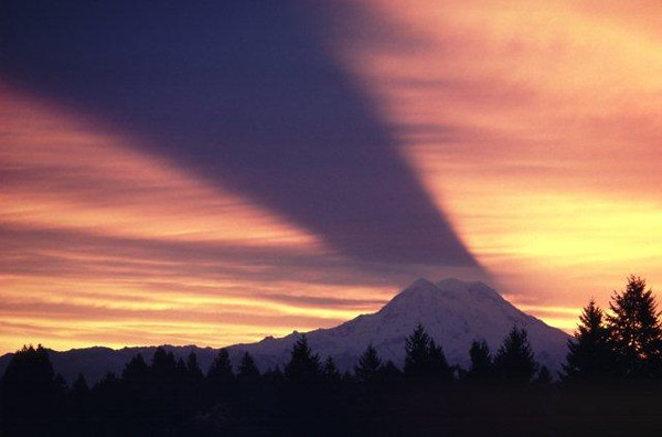 """When the sun rises behind Mt. Rainier, the shadow of the mountain is sometimes projected on the high clouds above. This phenomenon is very rare and when it occurs it is far more important to be """"out there"""" than it is to be in any special location."""
