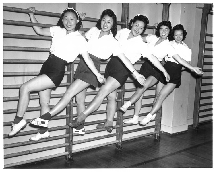 """""""A group of Japanese girls 'limber up' at gymnasium in the Japanese quarter of Los Angeles.  Left to right:  Sue Noma, Maye Noma, Lily Takeda, Shigeko Oi, and Meri Taniguchi.  All are Nisei.""""--caption on photograph"""