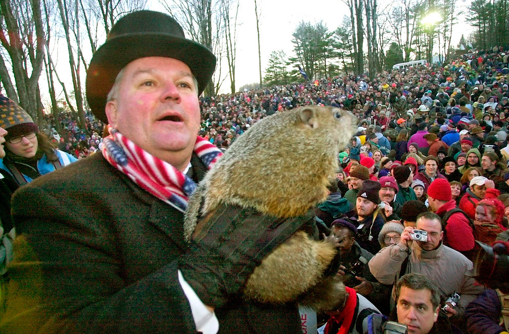 . Punxsutawney Phil is held by handler Bill Deeley after emerging from his Gobbler\'s Knob burrow at sunrise Saturday, Feb. 2, 2002 before a record crowd of some 25,000 in Punxsutawney, Pa.  Phil saw his shadow and predicted six more weeks of winter weather.  (AP Photo/Gene J. Puskar)