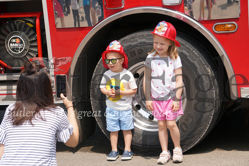 Photo by J.W. Johnson Jr. Henry and Norah Cross pose for a photo taken by Nicole Cross in front of a Harmony fire engine Saturday at the annual Big Truck Day in Zelienople Community Park.