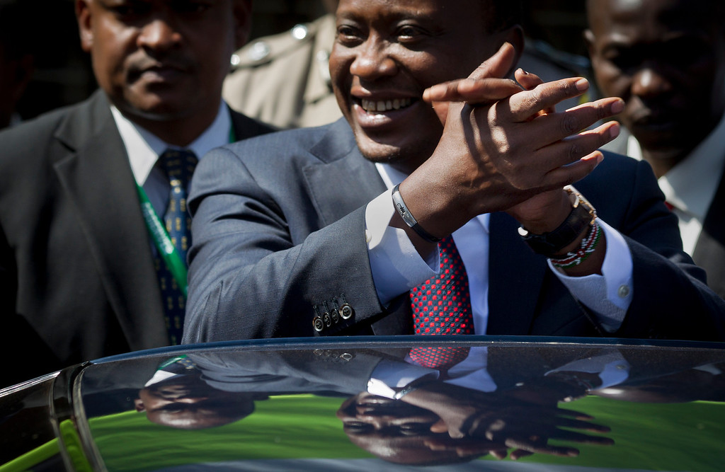 . Kenya\'s President-Elect Uhuru Kenyatta clasps his hands together as a gesture to supporters after leaving the National Election Center where final election results were announced declaring he would be the country\'s next president, in Nairobi, Kenya Saturday, March 9, 2013. (AP Photo/Ben Curtis)