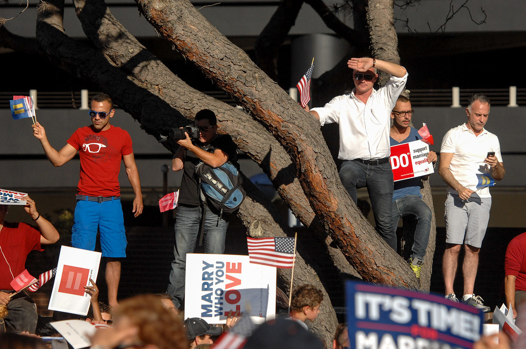 . People stand on a wall to view the speakers at the rally in West Hollywood to celebrate the U.S. Supreme Court\'s ruling that killed Prop 8, Wednesday, June 26, 2013. (Michael Owen Baker/L.A. Daily News)