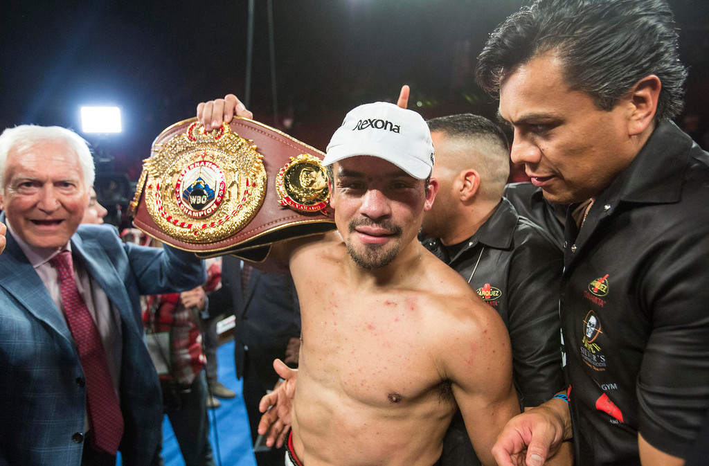 . Juan Manuel Márquez, of Mexico, celebrates with championship belt after his victory over Mike Alvarado in the tenth round of a WBO welterweight title boxing match at the Forum in Inglewood, Calif., Saturday, May 17, 2014.  (AP Photo/Ringo H.W. Chiu)